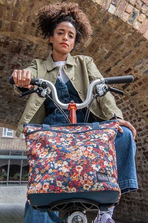 Girl on bike with floral bag.