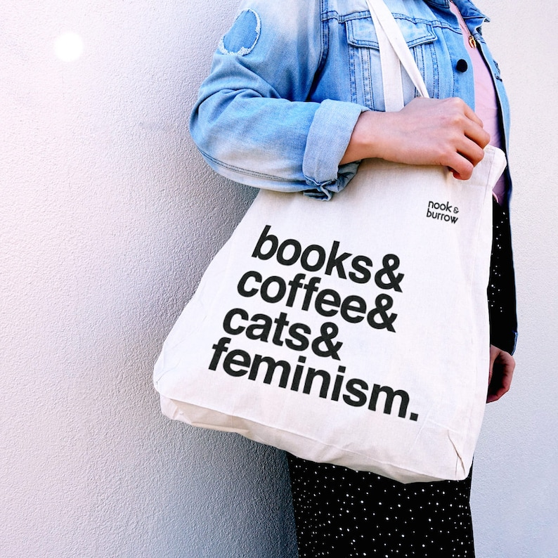Cream canvas tote with printed text saying 'books & coffee & cats & feminism'