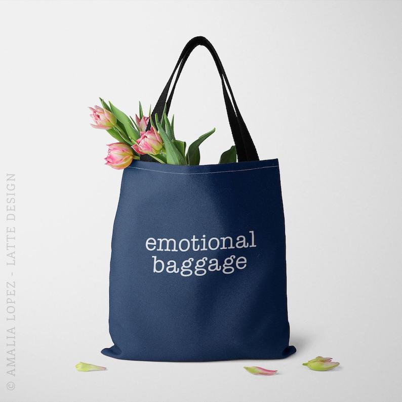 Navy tote bag with printed slogan that says Emotional Baggage