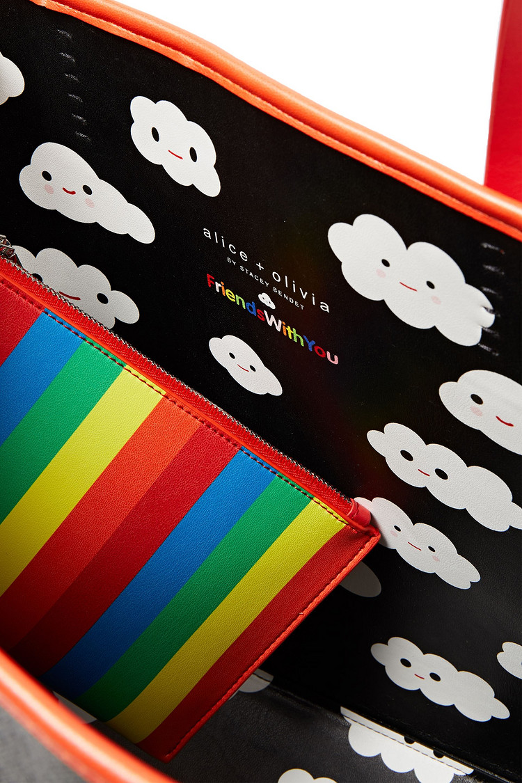 Photo shows interior of Friends With You Tote. Features a rainbow striped pocket and smiley-faced cloud lining.
